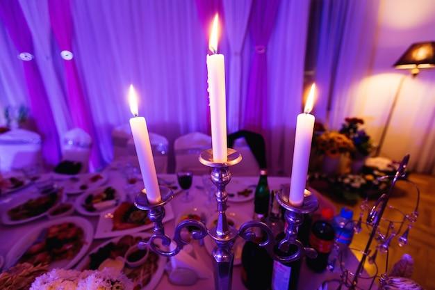 結婚式のテーブルの高級レストランで照明3つのキャンドル