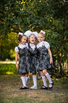 学校の制服を着た3人の女の子が校庭でポーズ