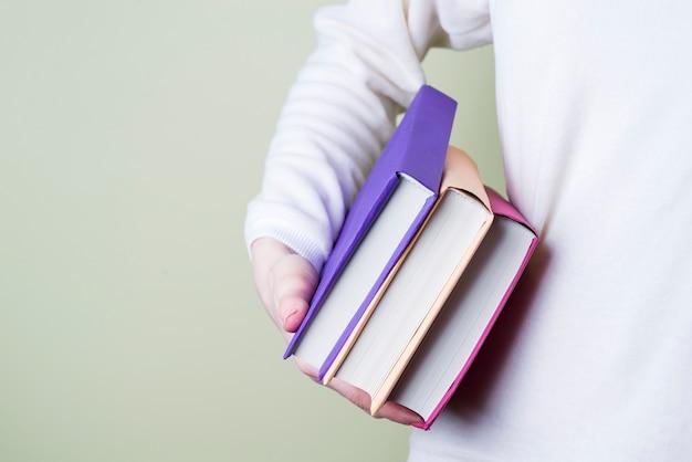 3色の本を持っている手のクローズアップ
