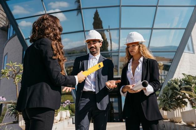 ガラス製のビルディングの前で話す3人の建築家