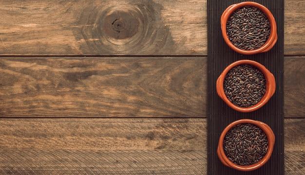 木製のテーブル上の皿の上に玄米を入れた3つのボールのボウル
