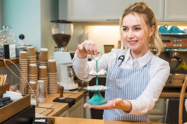 コーヒーショップでトレイを3層にメレンゲと砂糖の立方体を保持している若い女性の笑みを浮かべてください。