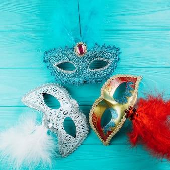 木製のテーブルの上の羽を持つ仮面舞踏会カーニバルマスクの3種類