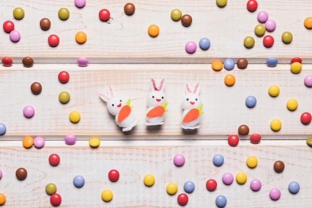木製のテーブルの上のカラフルな宝石キャンディーと中央の3つの白いウサギ