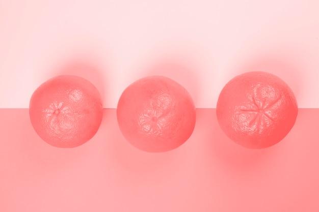 ピンクの背景に3つのグレープフルーツ全体の高架ビュー