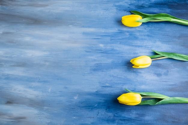 青いテーブルの上の3つのチューリップの花
