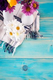 木製のテーブルの上の明るい花と3つの花瓶