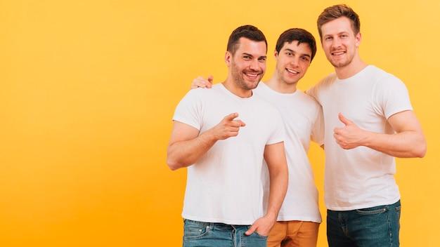 黄色の背景に対して立っている若い3人の男性の友人の肖像画を笑顔