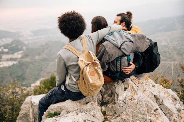 ビューを見て山の頂上に座っている3人の友人のグループ