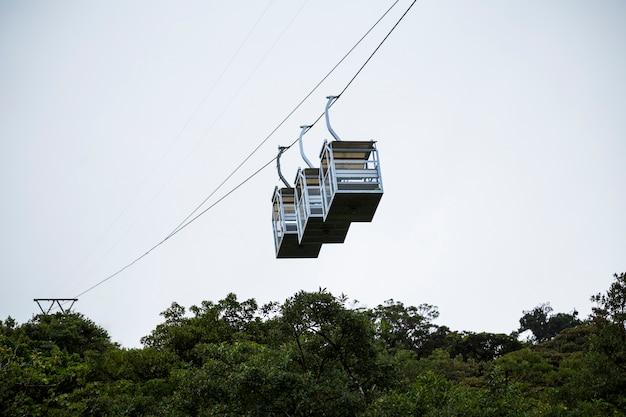 コスタリカの熱帯雨林の上の3つの空のケーブルカー