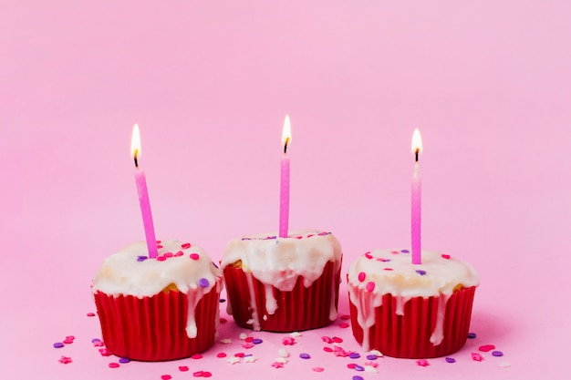 点灯ろうそくと3つのカップケーキ