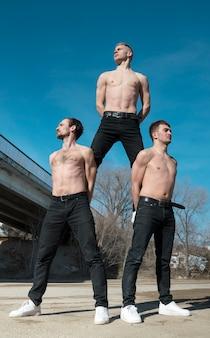 ダンスの前にポーズをとって3人の上半身裸のヒップホップのパフォーマーの正面図
