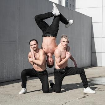 ダンスしながらポーズをとる上半身裸のヒップホップの3人のパフォーマー