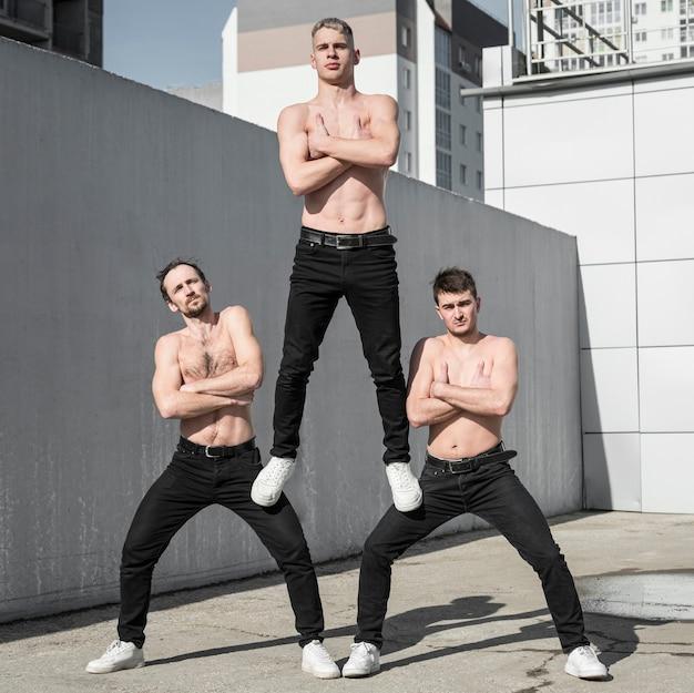 3人の上半身裸のヒップホップパフォーマーが一緒にポーズ