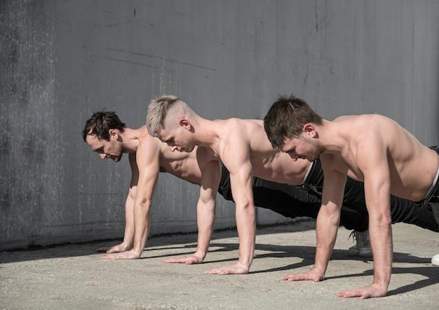 外でリハーサルする3人の上半身裸のヒップホップダンサー