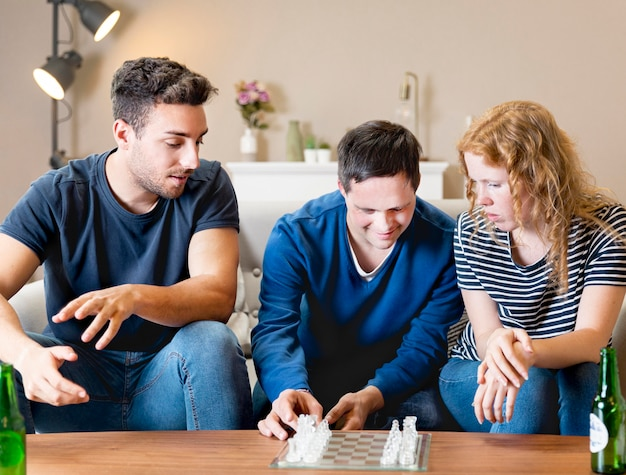 チェスをする家庭で3人の友人の正面図