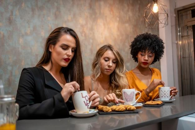 コーヒーショップでコーヒーを飲んでいる3つのガールフレンドの多民族のライフスタイル