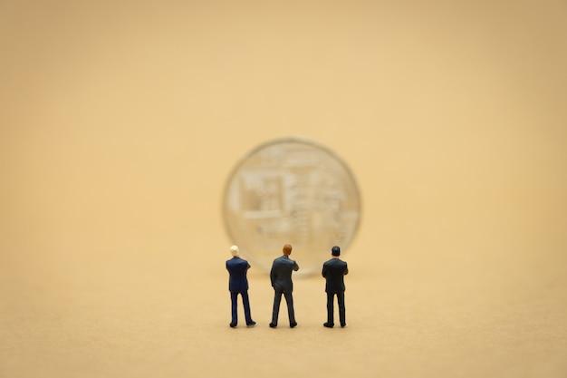 背中合わせに立っているミニチュア3人ビジネスマンビジネスでの交渉。
