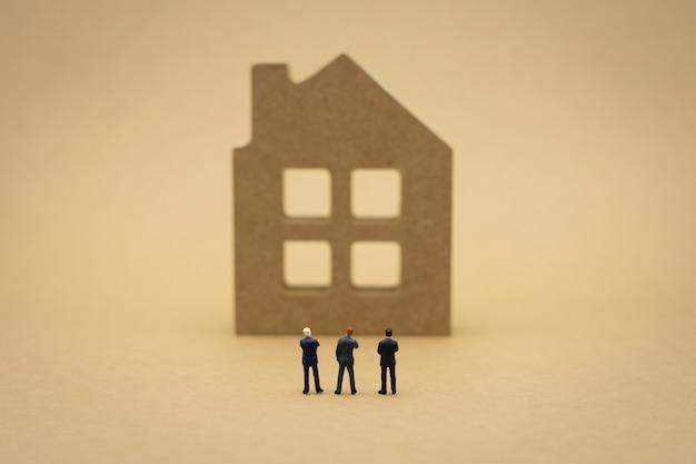 Миниатюрные 3-х человек бизнесмены, стоящие со спиной ведение переговоров в бизнесе.