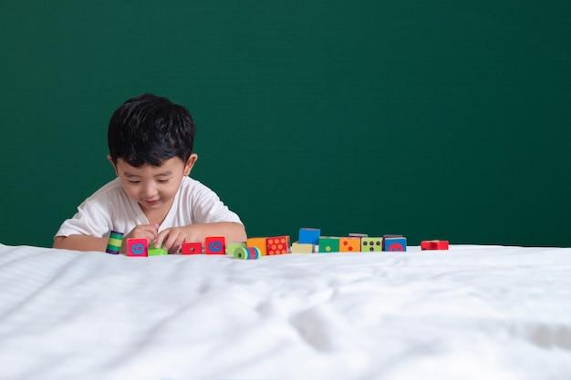 3歳のアジアの少年は、緑の黒板または教育委員会の背景におもちゃや正方形のブロックパズルをプレイ