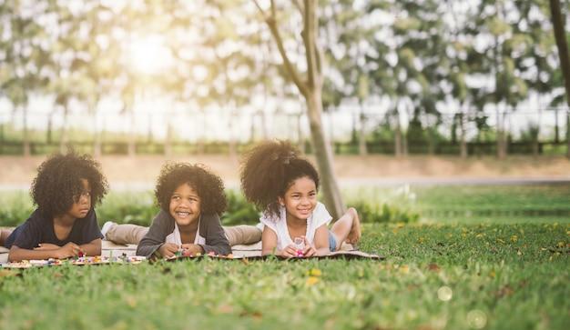 公園の草の上に横たわっている幸せな3人の小さな友達