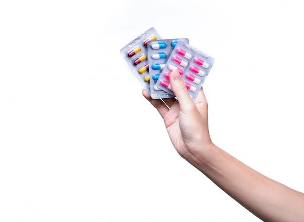ブリスターパックに抗生物質薬を持っているアジアの大人の手。女性の手は、カプセル薬の3つのパックを保持します。分離された抗生物質薬を与える手。