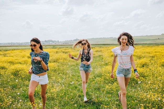 黄色の花の分野で3美しいヒッピーの女の子