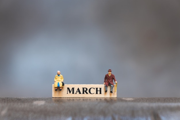 ミニチュアの人々、年配の男性と女性の3月の木製カレンダーの上に座って