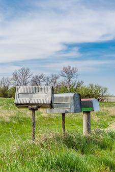 カナダのサスカチュワン州農村部の大草原の上の3つの古い金属農家のメールボックスの行