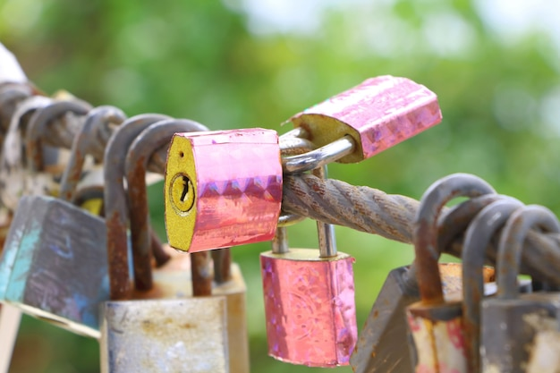 ピンクのステッカーと錆びた鉄の塀が付いている多くの古い錆の鍵ロックが付いている3つの鍵カバー