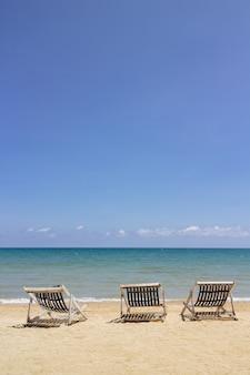 海と明るい空とバックグラウンドでトラットのコ・マックでビーチに3つの折りたたみビーチチェア