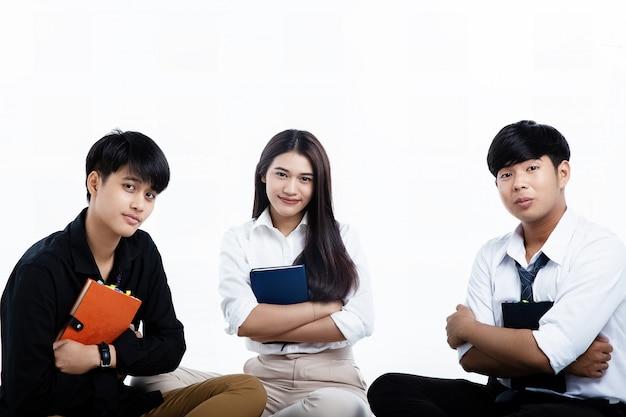 本を両腕に抱えている3人の若いティーンエイジャーは、試験の見直しの準備をします