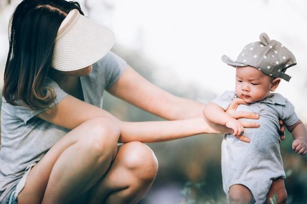 Портрет азиатской матери усмехаясь с ее ребёнком 3 месяцев старым на зеленой траве напольной в парке.