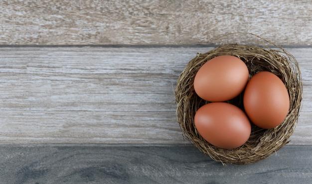ヴィンテージの木製テーブルの上の鳥の巣の農産物から3つの天然鶏の卵をグループ化します。広告イメージイースターまたは空き領域を持つ食品のコンセプト。