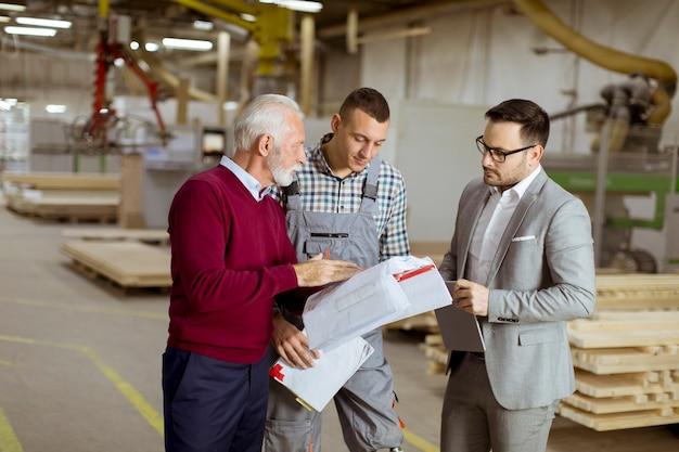 3人の男性が立って、家具工場で話し合います