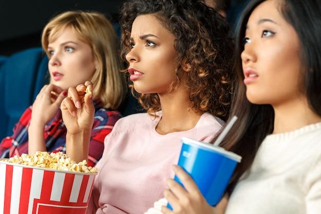 映画の魔法!映画館に注意深く座って映画を見ている3人の美しい女性の友人のクローズアップショット