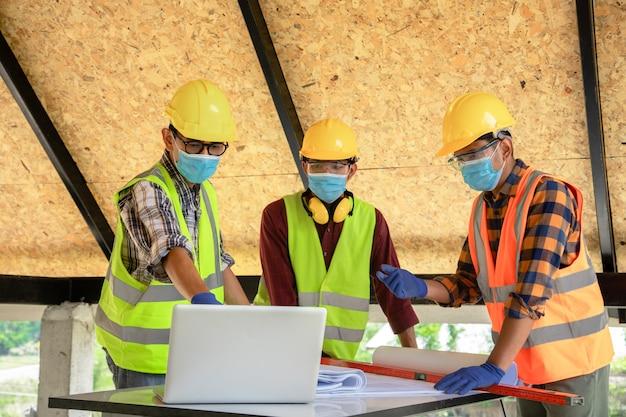 建設エンジニアと3人の建築家のチームが医療用マスクを着用する準備ができています。