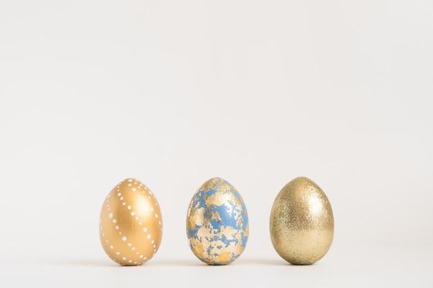 青い表面に3つの黄金のイースターエッグが飾られています。最小限のイースターコンセプト。