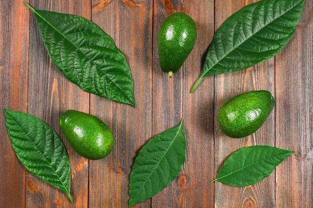葉を持つ3つの緑の生熟したアボカドは、茶色の木製のテーブルの上にあります。平置き。上面図。