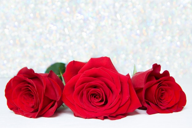 背景のボケ味を持つ3つの赤いバラ