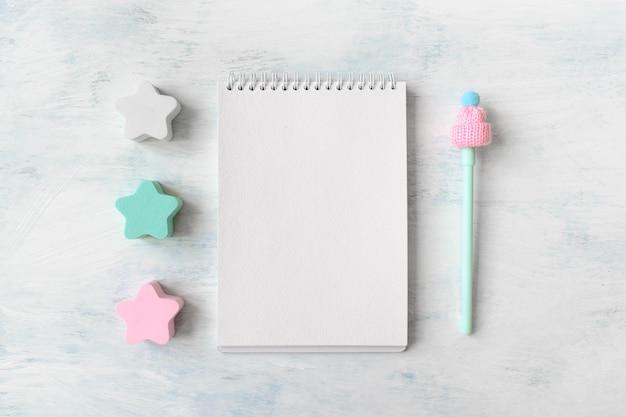 開いた白の3つのパステルブルーとピンクの星、ノートブック、ペンと冬のモックアップ