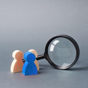 灰色の虫眼鏡の近くに立つ3つの木製人間図