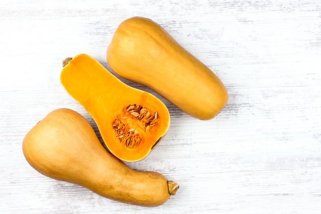 白いテーブルの上のカボチャ。甘い洋ナシの形の3つのオレンジ色のカボチャ