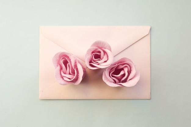 白い封筒、青い背景に3つのピンクのバラの花。ミニマルフラットレイ