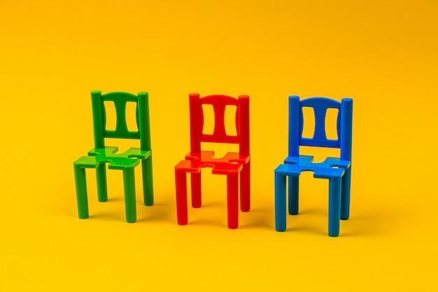 黄色の背景に異なる色の3つのプラスチックのおもちゃの椅子