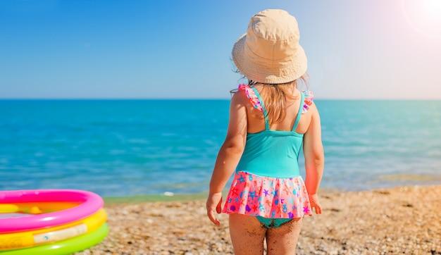 Маленькая девочка 3-х лет в солнце шляпу и купальник на пляже, глядя на море в солнечный день.