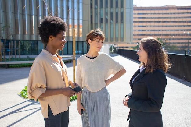 通りに立っているスマートフォンを持つ3人の女性