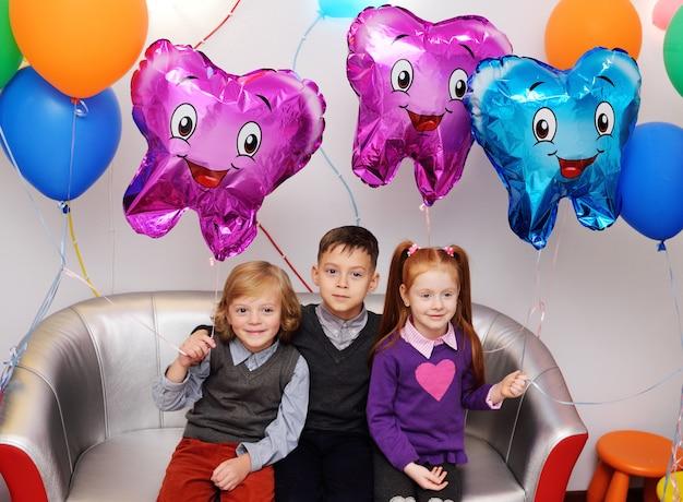 3人の子供が歯の形の風船のあるソファに座っています。