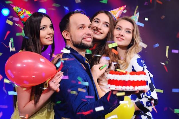 男と3人の女の子が歓喜し、ナイトクラブでパーティーを祝う