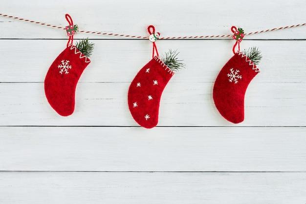 白い木製の背景にロープにぶら下がっているモミの木で飾られた3つの赤いクリスマスソックス。コピースペース